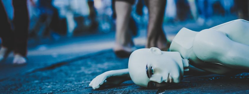 mannequin lying on the street while people walk past without paying attention