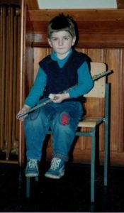 Gwydion Blackrose at 7 years old sitting with a transverse flute
