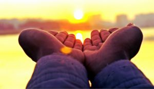 hands of a black person greeting the sun