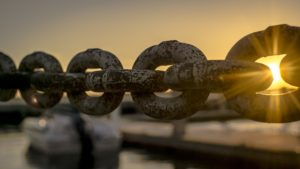 the sun coming out behind rusting chains
