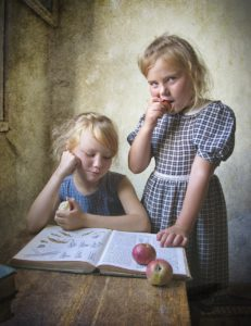 two girls in simple clothing learning from a book