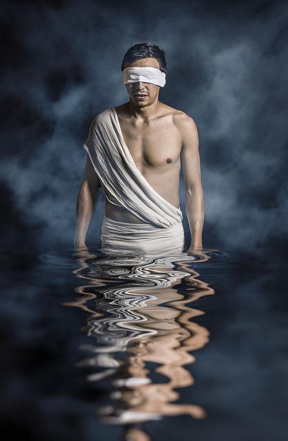 Blindfolded man walking through water