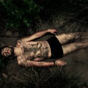 Half-naked man covered with mud and meditating within nature