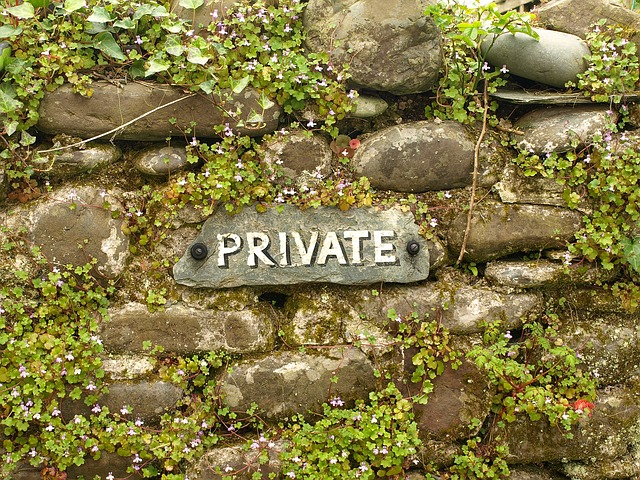 overgrown rocks with a sign saying private