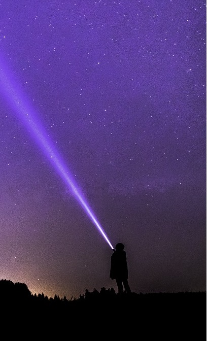 kid with a flashlight pointing up towards the night sky at the extraterrestrials